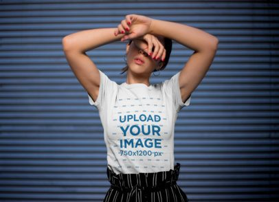 T-Shirt Mockup of a Stylish Woman Posing in Front of a Blue Wall 20688