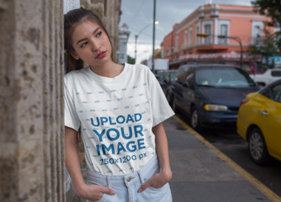 T-Shirt Mockup of a Serious Girl Leaning Against a Stone Building 22960
