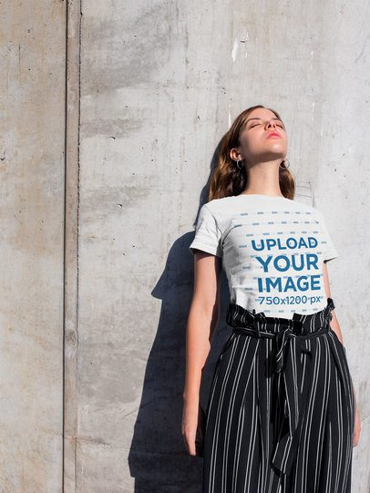 T-Shirt Mockup of a Girl Standing Against a Concrete Wall 20698