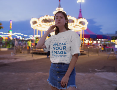 Tshirt Mockup of a Woman Standing Against a Carousel 22973