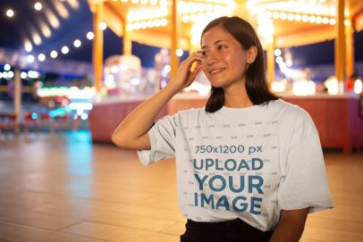 Mockup of a Smiling Girl Wearing a Tshirt by a Carousel 22977