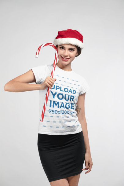 Christmas T-Shirt Mockup Featuring a Smiling Woman Wearing a Santa Hat and Holding a Candy Cane 23889