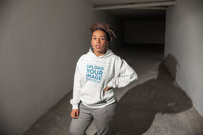 Mockup of a Woman with Locs Wearing a Hoodie in a Dark Hallway 23427