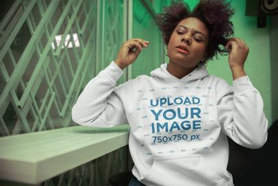 Mockup of a Girl with an Afro Wearing a Hoodie in a Place with Green Light 23492