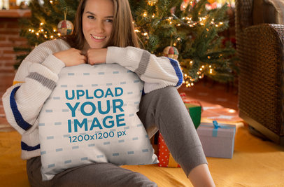 Mockup of a Cute Girl Holding a Pillow in Front of the Christmas Tree 23505