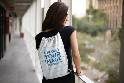 Drawstring Bag Mockup Featuring a Girl in an Open Hallway 23665