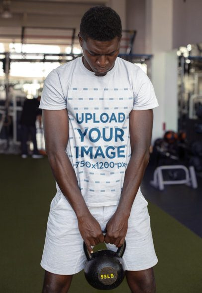 Round Neck Tee Mockup of a Strong Man Holding a Kettlebell at the Gym 23641