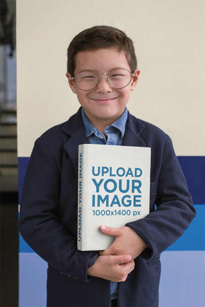 Mockup of a Young Smiling Boy Holding A Book to His Chest 23728