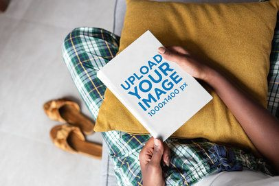 Mockup of a Book Held by a Woman's Hands on a Couch 23695
