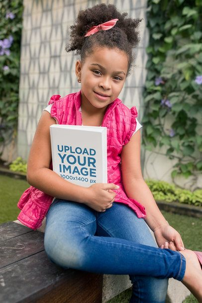 Mockup of a Little Girl Holding a Book in Her Backyard 23714