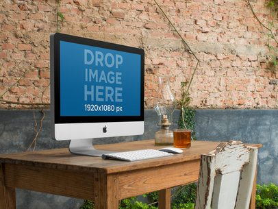 iMac on Top of a Wooden Desk at a Creative Office Mockup a4865