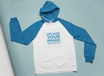 Mockup of a Raglan Hoodie in Flat Lay Position over a Colored Cardboard 24377