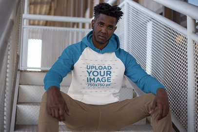 Raglan Pullover Hoodie Mockup of a Man Sitting on a Stairway 24121