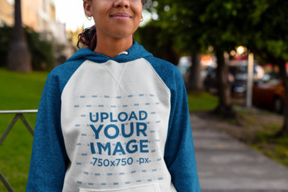 Mockup of a Woman Wearing a Raglan Hoodie on a Sidewalk 24174