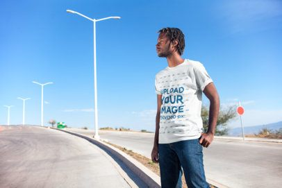 Mockup of a Man Wearing a T-Shirt on an Empty Road 20047
