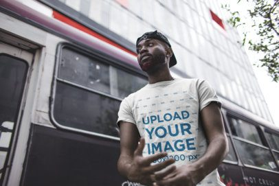 Mockup of a Man Wearing a Tee in Front of a City Bus 21680