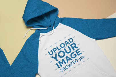 Mockup of a Heathered Raglan Hoodie Lying Flat over Pasteboards 24731