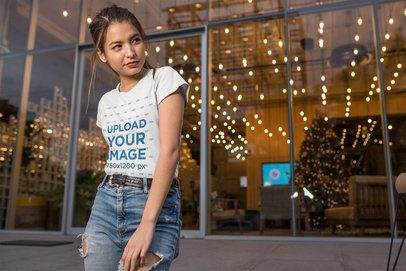Mockup of a Woman Wearing a T-Shirt and Ripped Jeans in Front of an Office Lobby 24650