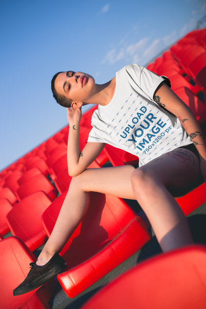 T-Shirt Mockup of an Alternative Woman With a Moon Tattoo Against Red Chairs 20184