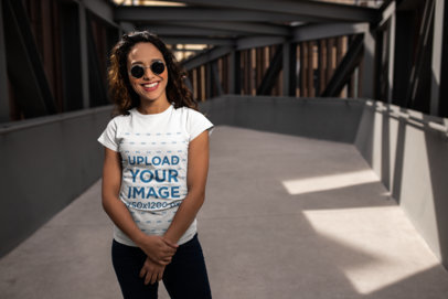 T-Shirt Mockup of a Smiling Woman with Cool Sunglasses Posing Casually 24656