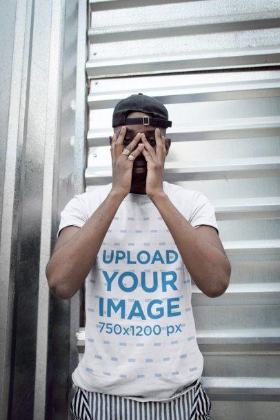 T-Shirt Mockup of a Man Hiding His Face Against a Metal Door 21683