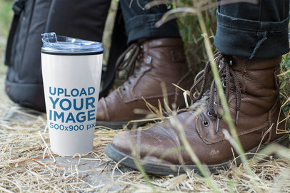 Mockup of a Travel Mug Next to a Man Wearing Leather Boots 24389