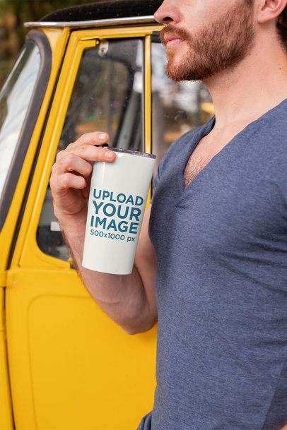 Mockup of a Man Holding a Travel Mug by a Yellow Car 24396