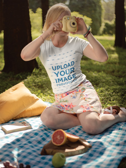 T-Shirt Mockup of a Girl Taking a Photo with a Polaroid Outdoors 21994