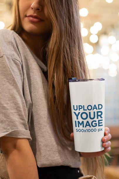 Mockup of a Woman Holding a Travel Mug Indoors 24349