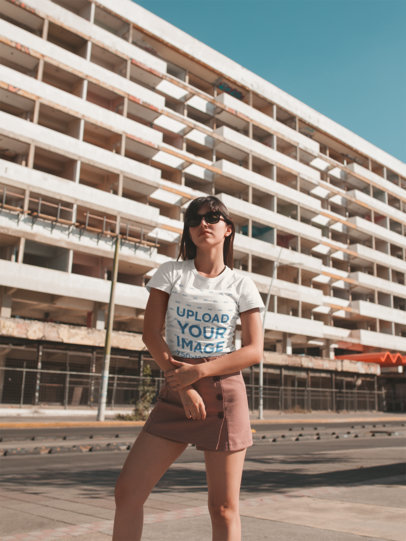 Mockup of a Girl Wearing a T-Shirt Outside a White Building 19613
