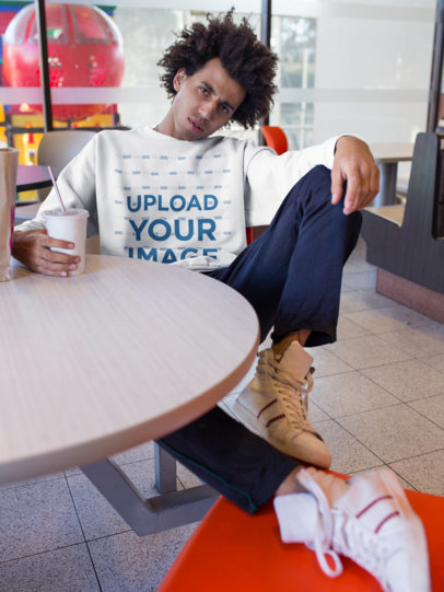 Mockup of a Man with an Afro Wearing a Sweatshirt in a Fast Food Restaurant 18339