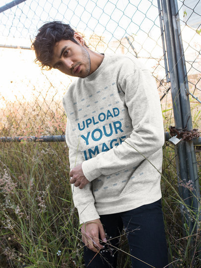 Crewneck Sweater Mockup of a Man Standing by a Fence 18191