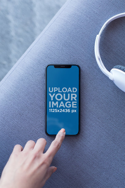 Mockup of an iPhone X Resting on a Couch Playing a Podcast 24793