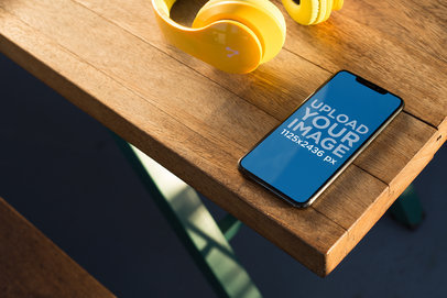 Mockup of an iPhone X Resting on a Wooden Table 24799
