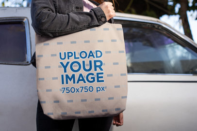Mockup of a Woman Carrying a Tote Bag in Front of an Abandoned Car 24880
