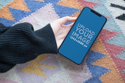 Mockup of a Woman's Hand Holding an iPhone XS Max Over a Carpet 25367