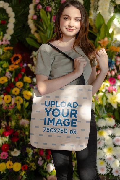 Tote Bag Mockup of a Girl Posing in Front of Flower Arrangements 24873