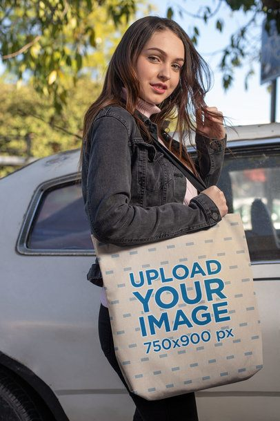 Tote Bag Mockup of a Girl Smiling and Fixing Her Hair Beside an Old Car 24879