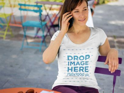 T-Shirt Mockup of a Woman Sitting at an Outdoor Table 5686a