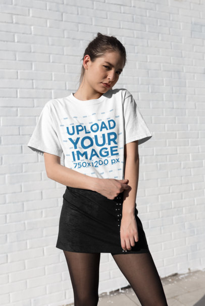 Tee Mockup Featuring a Cute Shy Girl Posing in Front of a Brick Wall 25785