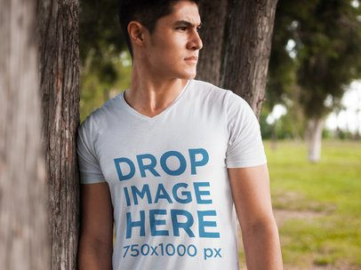 T-Shirt Mockup of a Young Man Leaning Against a Tree 5556a