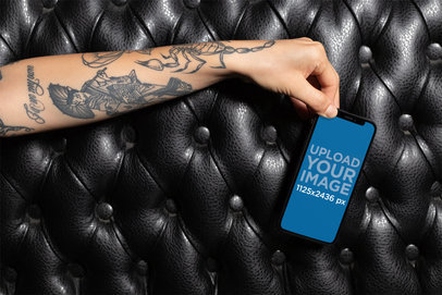 iPhone XS Mockup of a Tattooed Hand Over a Black Leather Sofa 25377