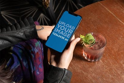 iPhone XS Mockup Featuring a Woman Having a Cocktail 25379
