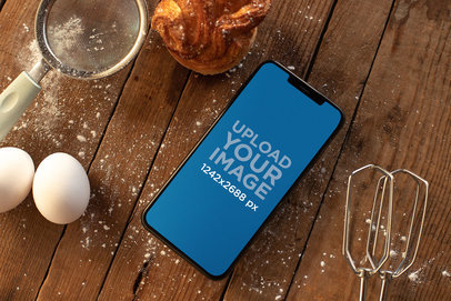 iPhone XS Max Mockup over a Wooden Surface Surrounded by Baking Supplies 25491