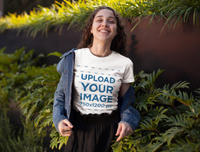 T-Shirt Mockup of a Smiling Curly-Haired Girl Standing by Some Bushes 25799
