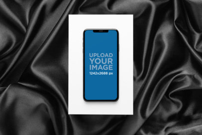 iPhone XS Max Mockup over a Cardboard Surrounded by a Dark Fabric 25959
