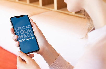 Over-The-Shoulder View Mockup of a Blonde Girl Looking at Her iPhone XS 25439