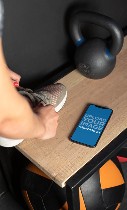 Mockup of a Fitness Girl Tying Her Sneaker on a Bench Next to an iPhone XS Max 25982