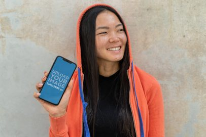 iPhone XS Max Mockup Featuring a Smiling Woman with a Hoodie 25774