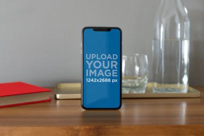 iPhone XS Max Mockup Standing Next to Some Glass Recipients 25897